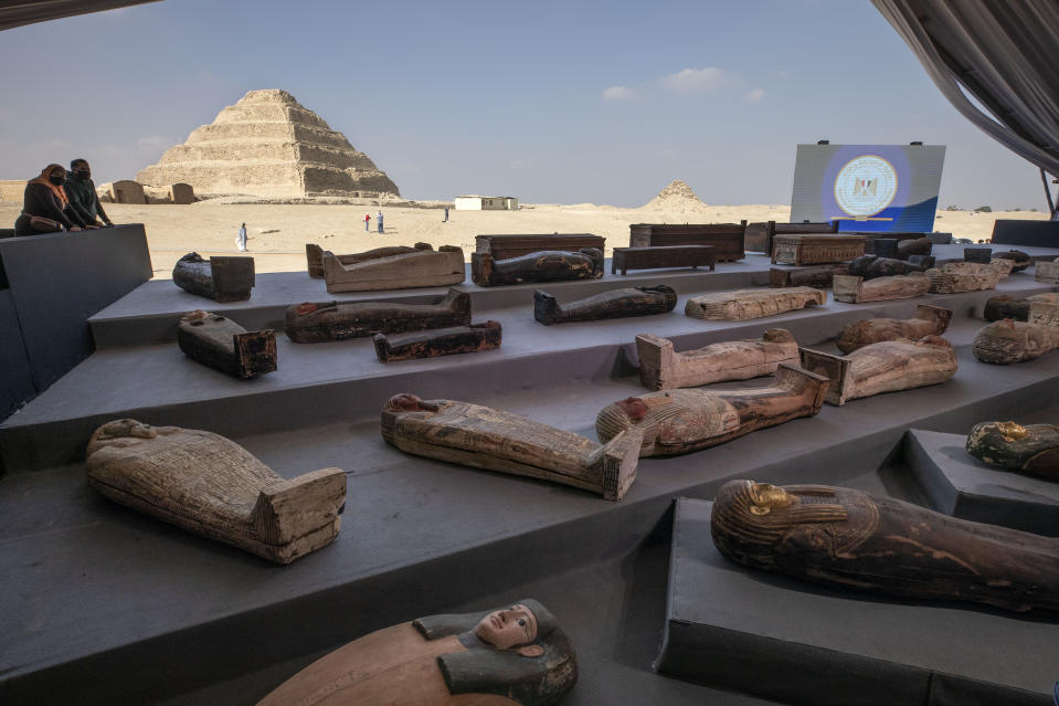 People look at ancient sarcophagi on display, discovered in a vast necropolis in Saqqara, Giza, Egypt, Saturday, Nov. 14, 2020. Egyptian antiquities officials on Saturday announced the discovery of at least 100 ancient coffins, some with mummies inside, and around 40 gilded statues south of Cairo. (AP Photo/Nariman El-Mofty)