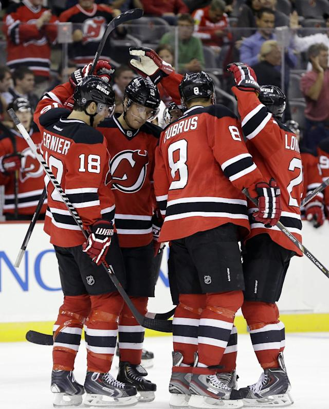 New Jersey Devils players, from left, Steve Bernier (18), Adam Larsson (5), of Sweden, Dainius Zubrus (8), of Lithuania, and Andrei Loktionov (21), of Russia, celebrate a goal by Zubrus during the second period of an NHL preseason hockey game against the Philadelphia Flyers, Thursday, Sept. 26, 2013, in Newark, N.J. (AP Photo/Julio Cortez)
