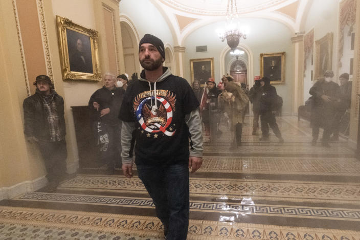 FILE - In this Jan. 6, 2021, file photo, smoke fills the walkway outside the Senate Chamber as supporters of President Donald Trump are confronted by U.S. Capitol Police officers inside the Capitol in Washington. Far-right social media users for weeks openly hinted in widely shared posts that chaos would erupt at the U.S. Capitol while Congress convened to certify the election results. (AP Photo/Manuel Balce Ceneta, File)