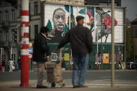 Two people stand in front of a mural of George Floyd, painted by Belgian artist Julien Crevaels, also known as NovaDead, in the center of Brussels, Wednesday, April 21, 2021. The guilty verdict in the trial over George Floyd's death was not just celebrated in America. It signaled hope for those seeking racial justice and fighting police brutality on the other side of the Atlantic, where Black Lives Matter has also become a rallying cry.(AP Photo/Francisco Seco)