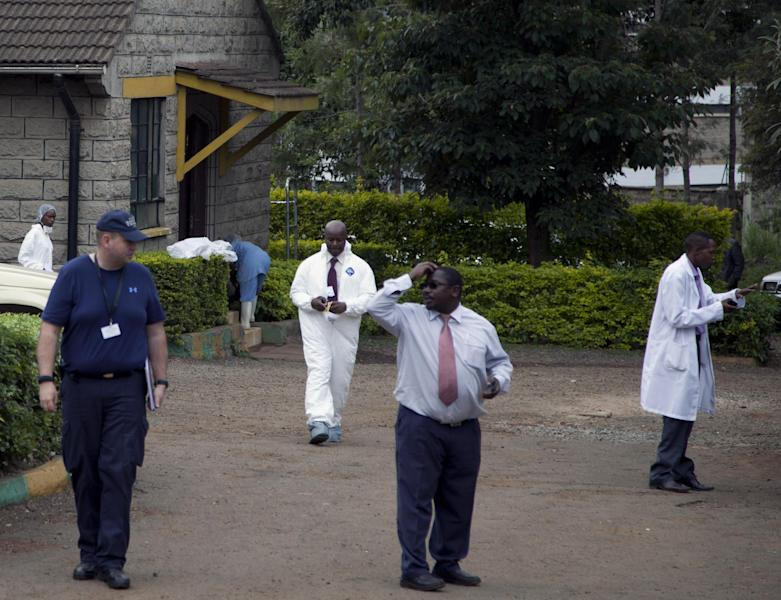 A foreign forensic examiner, left, with mortuary staff, at the Nairobi City Mortuary where a group have arrived to take DNA tests, in Nairobi, Wednesday, Oct. 2, 2013, following the attack on a shopping mall in the city that left at least 67 dead. (AP Photo/Sayyid Azim)