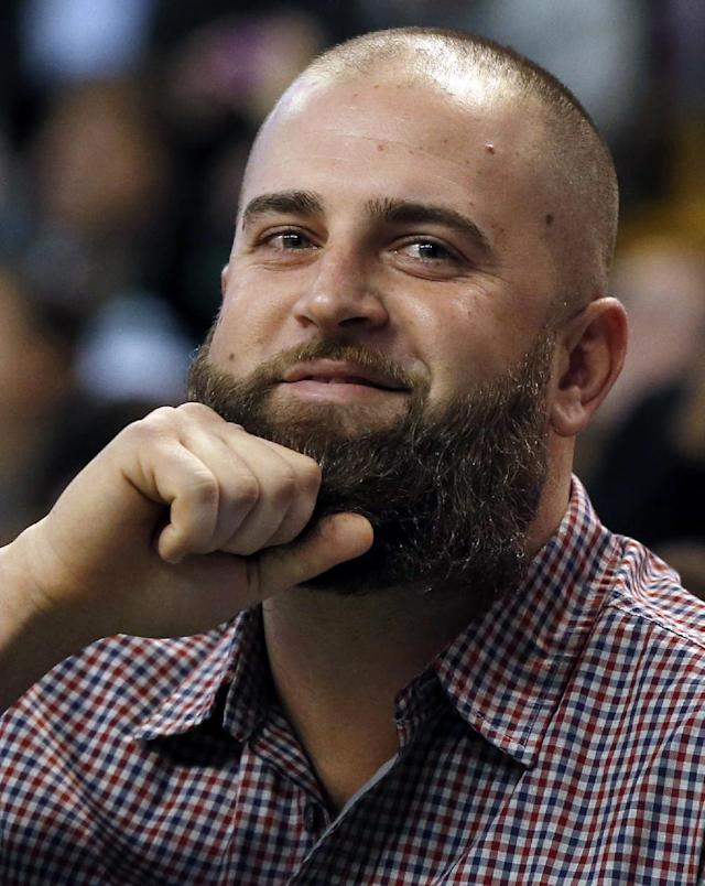 Boston Red Sox's Mike Napoli tugs on his beard for the cheering crowd as he sits courtside at an NBA basketball game between the Boston Celtics and the Charlotte Bobcats in Boston, Wednesday, Nov. 13, 2013. (AP Photo/Elise Amendola)