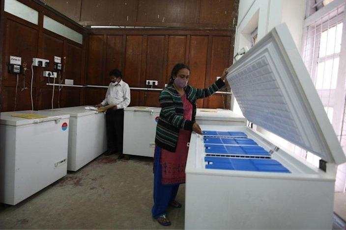 An Indian health official conducts routine checks of the Electronic Vaccine Intelligence Network (EVIN) ice line cold storage refrigerator at a city government hospital in Bangalore, India.