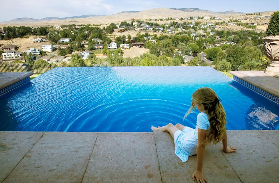 Francesca Williams, 11, dips her foot in the pool. The infinity edge makes it appear as if the water is magically contained. Homeowner and builder Cris hand-tiled the pool over the winter.  (Photo by Darin Oswald/Idaho Statesman/Tribune News Service via Getty Images)