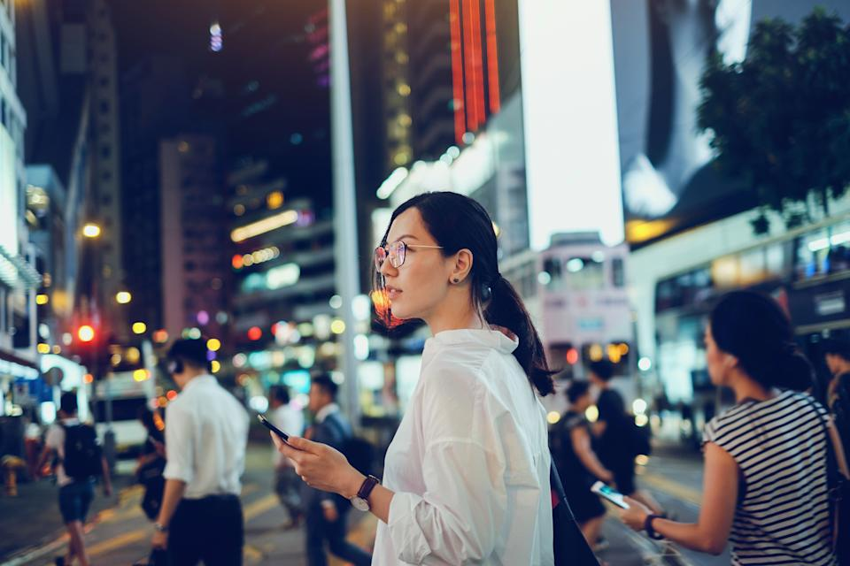 Beautiful Asian woman using mobile phone while crossing road in busy downtown city street at night (Photo: d3sign via Getty Images)