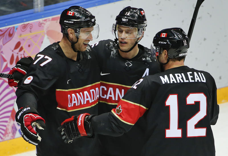 Canada forward Jeff Carter, left, is congratulated by forward Jonathan Toews and forward Patrick Marleau after scoring his second goal of the second period during a men's ice hockey game against Austria at the 2014 Winter Olympics, Friday, Feb. 14, 2014, in Sochi, Russia. (AP Photo/Julio Cortez)