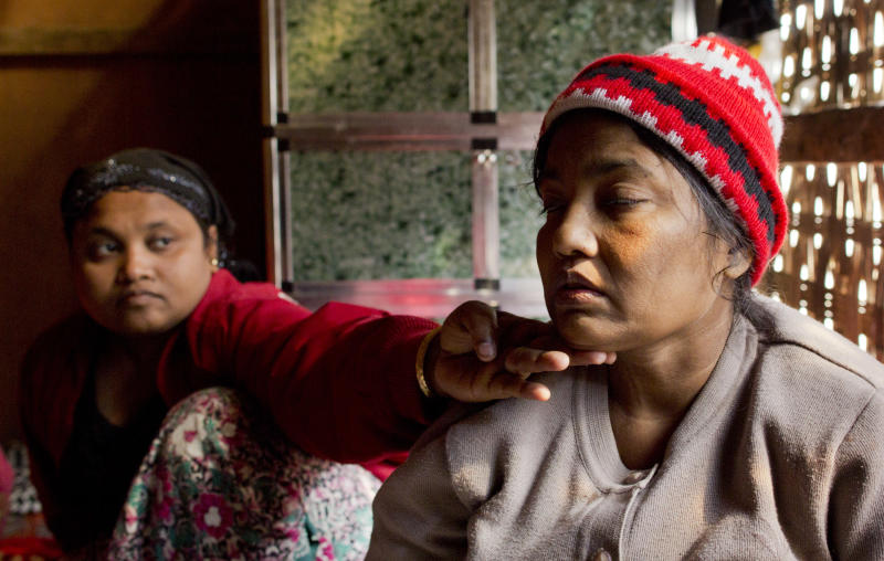 In this Jan. 17, 2014 photo, Raduan, left, helps her ailing mother Noor Jahan to steady her weak body at their living room in The' Chaung village in north of Sittwe, Rakhine state, Myanmar. As part of one of the community's richest families, Jahan, who later died, should have been in a hospital getting tests and medicine for her failing liver and kidneys, but it wasn't available to her. She was an ethnic Rohingya from Myanmar's northwestern state of Rakhine, forced to live segregated behind security checkpoints in a dirt-floor bamboo hut about a quarter mile from the sea. (AP Photo/Gemunu Amarasinghe)