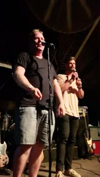Peter Helliar and Chris Hemsworth on stage at the Make It Rain fundraising event in Byron Bay