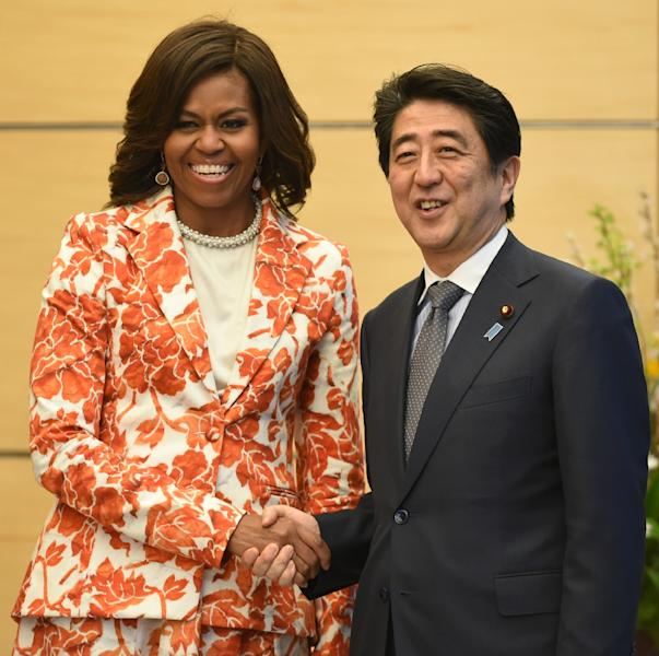 Michelle Obama is greeted by Shinzo Abe at Abe's official residence in Tokyo on March 19, 2015 (AFP Photo/Toshifumi Kitamura)