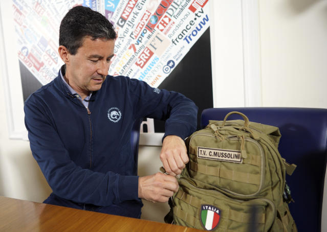 In this picture taken on Wednesday, May 8, 2019, Brothers of Italy party candidate for the upcoming European Parliament elections, Caio Giulio Cesare Mussolini, adjusts his backpack from when he was a Navy officer, during a press conference at the Foreign Press association, in Rome, Wednesday, May 8, 2019. Mussolini's name remains part of the political discourse, first with lawmaker Alessandra Mussolini, Benito Mussolini's granddaughter who started out with a now defunct neo-fascist party, and now with his great-grandson, Caio Giulio Cesare Mussolini, who is running with the far-right Brothers of Italy party in the European elections. (AP Photo/Andrew Medichini)