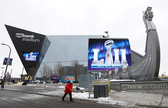 FILE PHOTO: A man walks by US Bank Stadium, home to this weekend's Super Bowl, in downtown Minneapolis, Minnesota, U.S., January 30, 2018. REUTERS/Kevin Lamarque/File Photo