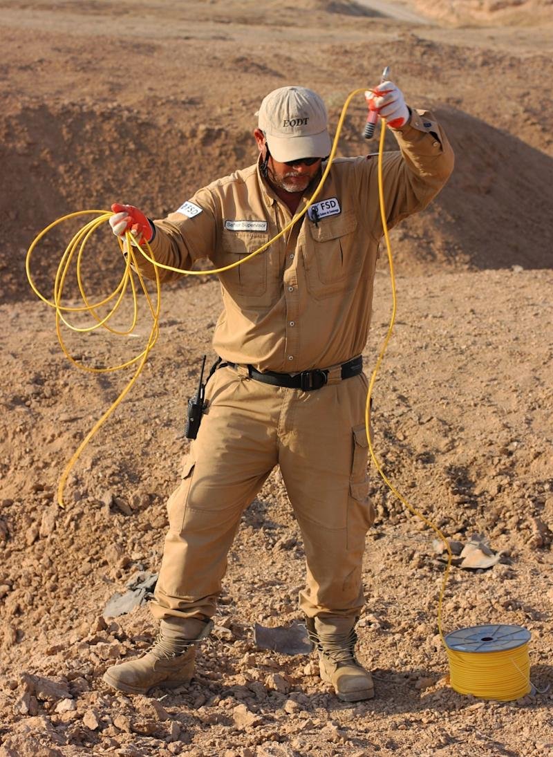 Just after dawn on Wednesday, the demining team rigs together the explosives it has collected in the previous week to detonate and destroy them behind the frontlines. The fortified positions are held by Kurdish Peshmerga forces. (Photo: Ash Gallagher for Yahoo News)