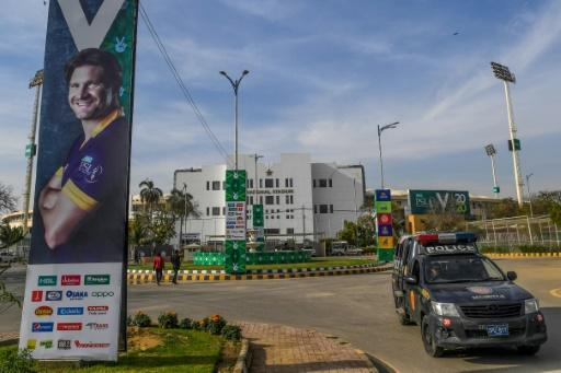 A police vehicle guards the National Stadium in Karachi alongside a poster of Australian star Shane Watson ahead of the Pakistan Super League season ebinning Thursday