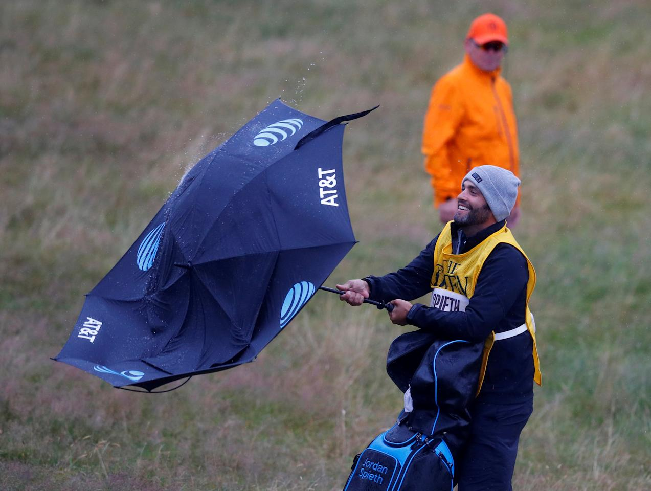 Golf - The 146th Open Championship - Royal Birkdale - Southport, Britain - July 21, 2017   The caddie of USA's Jordan Spieth has trouble with an umbrella on the 17th hole during the second round    REUTERS/Phil Noble