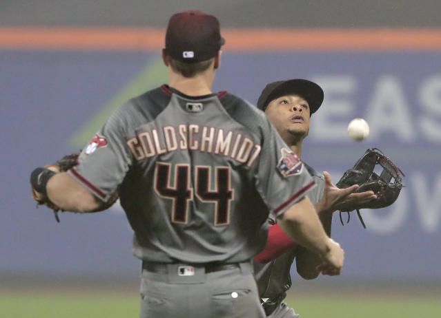 Arizona Diamondbacks shortstop Ketel Marte, right, makes a catch on a pop-up by New York Mets' Wilmer Flores to end the seventh inning of a baseball game, Saturday, May 19, 2018, in New York. (AP Photo/Julie Jacobson)