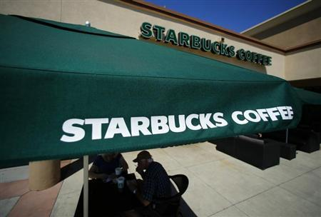 Customers enjoy their drinks outside a newly designed Starbucks coffee shop in Fountain Valley
