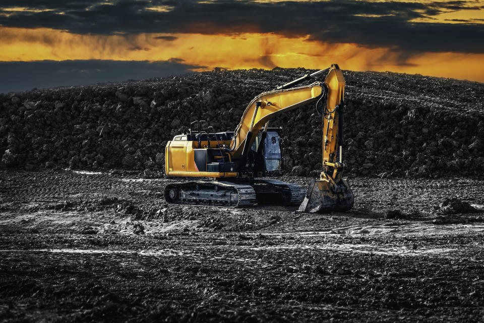 Excavator. Earth-Moving Heavy Equipment Construction side. Excavator on the construction side with a pile of land on the background. An Excavators are heavy construction equipment consisting of a boom, dipper, bucket and cab on a rotating platform known as the house.