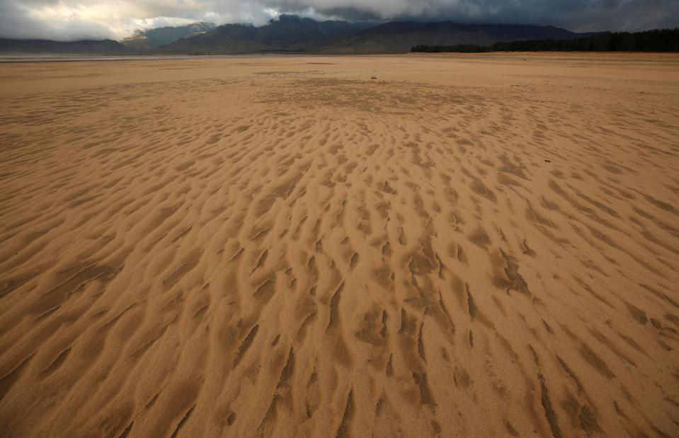 """Sand blows across a normally submerged area at Theewaterskloof dam near Cape Town, South Africa, January 20, 2018. The dam, which supplies most of Cape Town's potable water, is currently dangerously low as the city faces """"Day Zero"""", the point at which taps will be shut down accross the city.  Picture taken January 20, 2018. REUTERS/Mike Hutchings"""