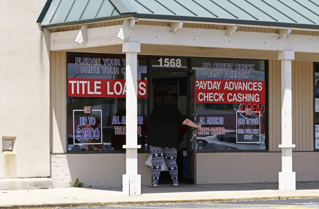 A woman enters an All American Check Cashing location in Brandon, Miss., Friday, May 12, 2017.  (AP Photo/Rogelio V. Solis)