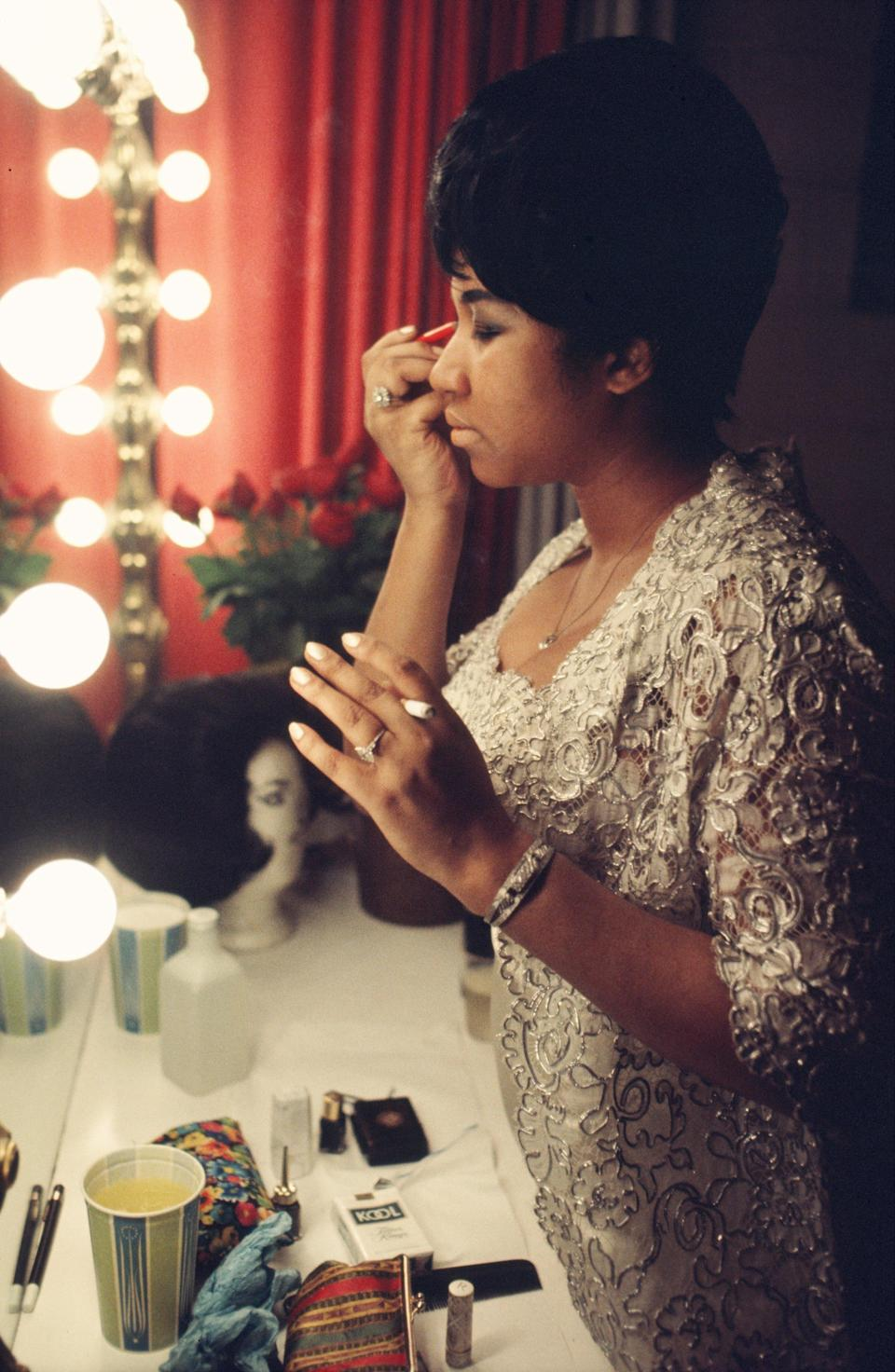 <p>Aretha Franklin fixes her makeup backstage, wearing a gold lace gown and delicate jewels, before a performance at Symphony Hall in Newark, N.J. (Photo by:Walter Iooss/Getty Images) </p>
