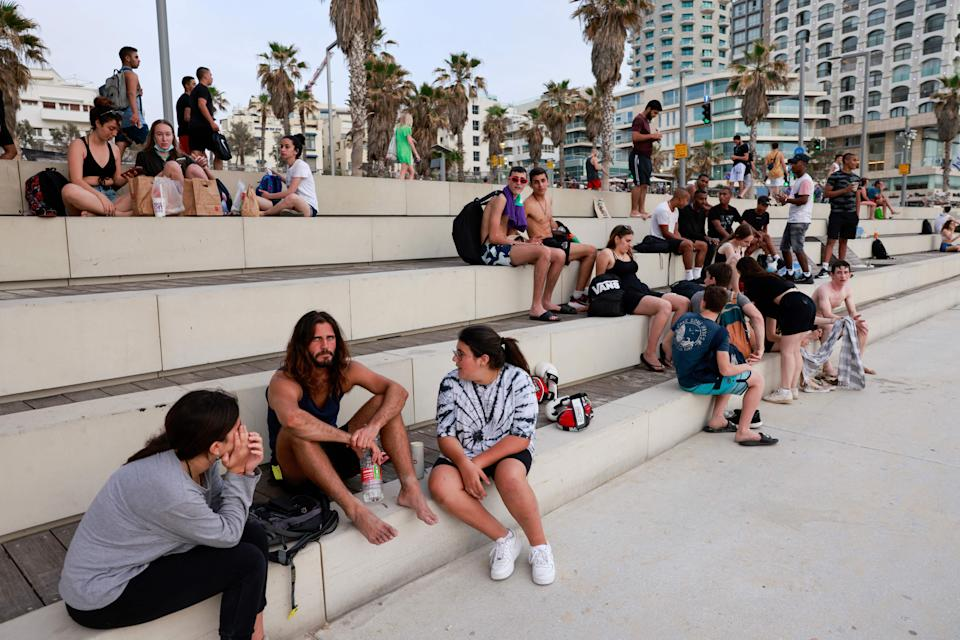 People relax in the Israeli coastal city of Tel Aviv on April 19, 2021, after authorities announced that face masks for COVID-19 prevention were no longer needed outside. - With more than half of the population fully vaccinated in one of the world's fastest COVID-19 inoculation campaigns, the number of coronavirus cases in Israel fell from some 10,000 new infections per day in mid-January to about 200 cases per day, which triggered an announcement from the Health Department on April 15 that face masks are no longer mandatory outdoors. (Photo by menahem kahana / AFP) (Photo by MENAHEM KAHANA/AFP via Getty Images)