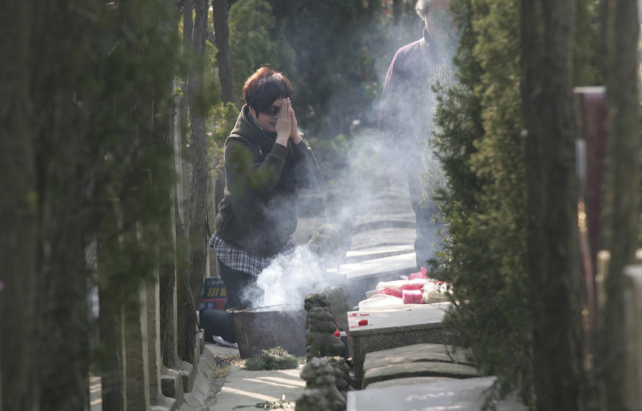 A woman offers prayer as she and her family members visit their family grave for Qingming Festival in Shanghai, China, Tuesday, April. 3, 2012, one day before the actual observance day. The Qingming Festival, a Chinese traditional festival also known as Pure Brightness Festival or Tomb Sweeping Day, falls on April 4 this year, the 15th day from the Spring Equinox. (AP Photo)