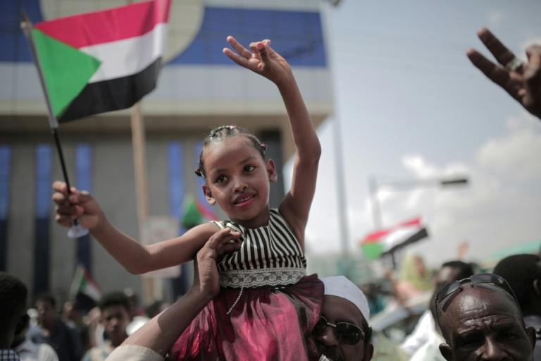 A young Sudanese girl waves the national flag in Khartoum as people celebrate the signing of the Constitutional Declaration after close to eight months of protests (AFP Photo/Jean Marc MOJON)