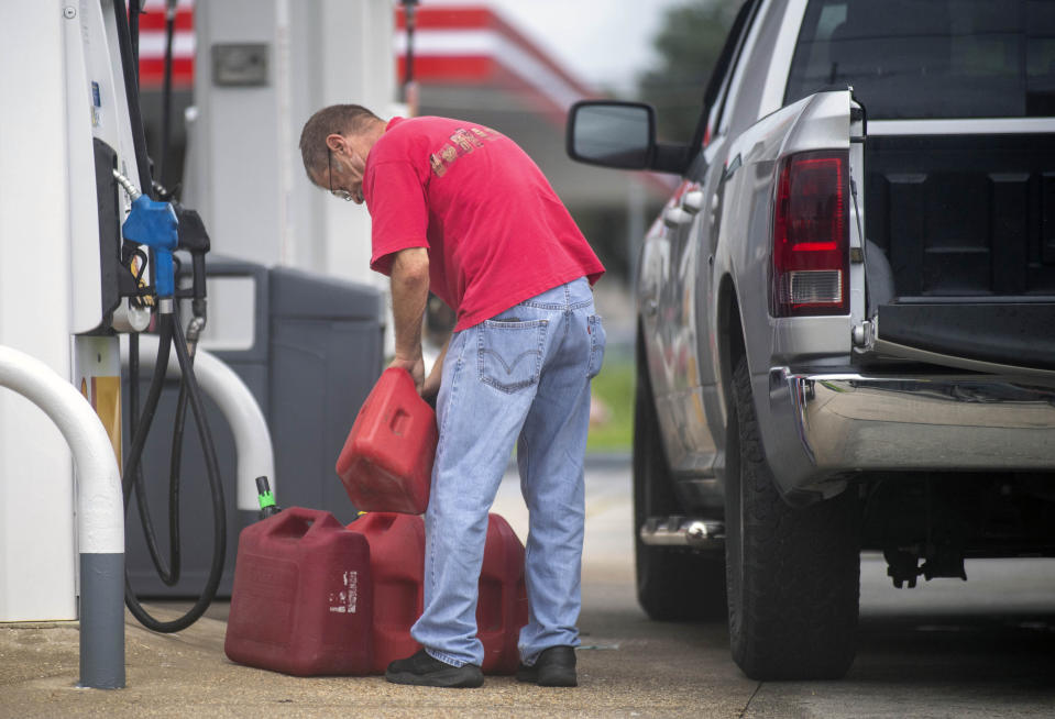 St. Bernard Parish residents fill up their cars and gas cans as the Louisiana coast prepares for the arrival of Hurricane Ida on Friday, Aug. 27, 2021 in New Orleans. Hurricane Ida struck Cuba on Friday and threatened to slam into Louisiana with devastating force over the weekend, prompting New Orleans' mayor to order everyone outside the protection of the city's levees to evacuate.(Chris Granger/The Times-Picayune/The New Orleans Advocate via AP)