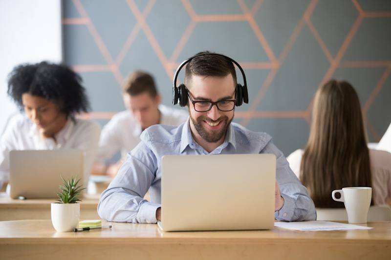 Smiling businessman listening to music while sitting at a laptop