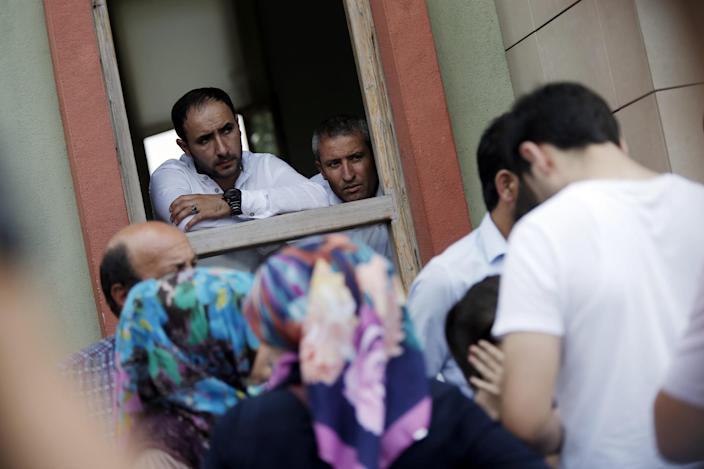 <p>Forensic officials look at family members of victims who are crying outside the Forensic Medical Center in Istanbul, Wednesday, June 29, 2016. (AP Photo/Emrah Gurel) </p>