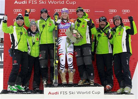 Maria Hoefl-Riesch of Germany (C) celebrates on the podium with her team after winning the women's FIS World Cup Downhill race in Cortina D'Ampezzo January 24, 2014. REUTERS/Alessandro Garofalo