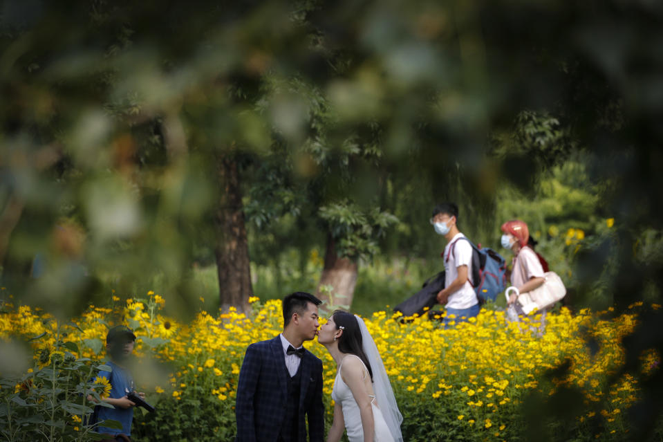 People wearing face masks to help curb the spread of the coronavirus pass by a newly weds kissing as they posing for wedding photos at the Olympic Forest Park in Beijing, Thursday, July 2, 2020. China reported three new cases of coronavirus, including just one case of local transmission in the capital Beijing, appearing to put the country where the virus was first detected late last year on course to eradicating it domestically, at least temporarily. (AP Photo/Andy Wong)