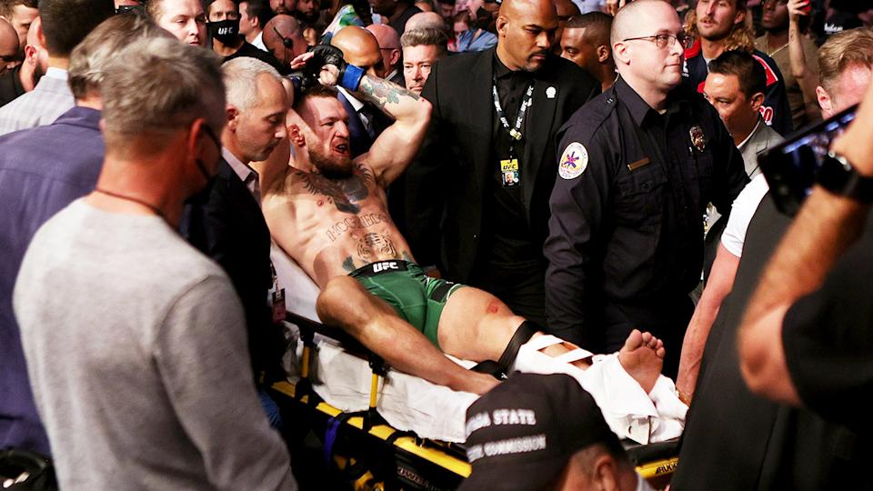 Conor McGregor, pictured here being carried out of the arena on a stretcher at UFC 264.
