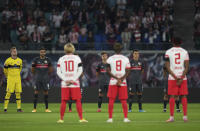 Players stand for a minute of silence prior to the German Bundesliga soccer match between RB Leipzig and VfB Stuttgart in Leipzig, Germany, Friday, Aug. 20, 2021. (AP Photo/Michael Sohn)