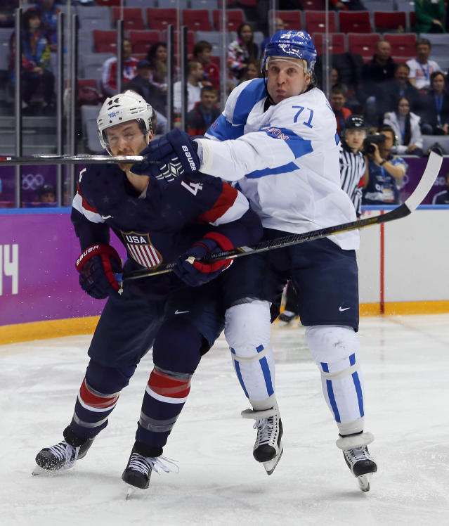 USA defenseman Brooks Orpik, left, and Finland forward Leo Komarov vie for the puck during the first period of the men's bronze medal ice hockey game at the 2014 Winter Olympics, Saturday, Feb. 22, 2014, in Sochi, Russia. (AP Photo/Petr David Josek)