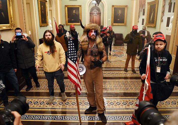 Jake Angeli, center in horned hat, is among supporters of President Donald Trump who breached security enter the Capitol on Jan. 6 as Congress meets to confirm the 2020 presidential election.