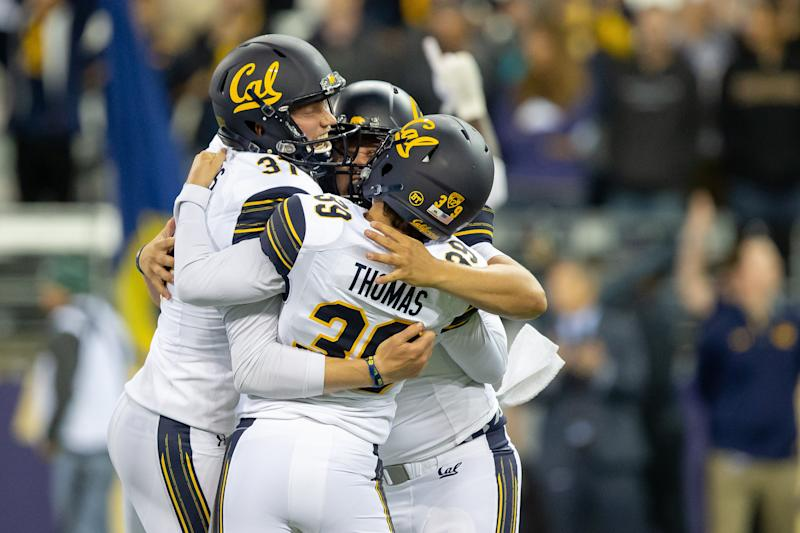Cal Bears kicker Greg Thomas (39) is hugged by teammates after kicking the game winning field goal late in the fourth quarter against Washington. (Getty)