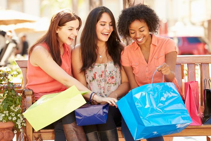 Three young women sitting on a bench and holding shopping bags