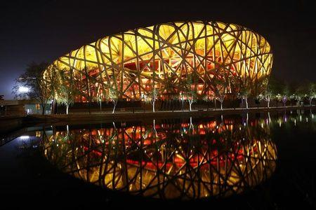 "National Stadium, also known as ""Bird's Nest"", is seen reflected in a lake before Earth Hour at Olympic Park in Beijing"
