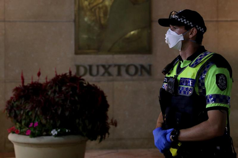 A police officer looks on as Australian passengers from Italian cruise liners arrive at the Duxton Hotel in central Perth. Source: AAP