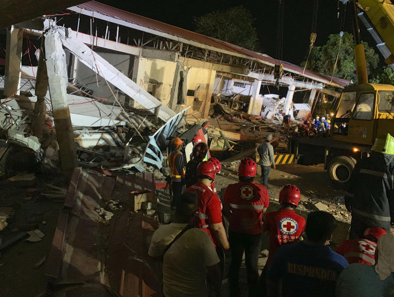 Workers continue rescue operations on people still trapped inside a collapsed building at Porac town, Pampanga province, northern Philippines Monday, April 22, 2019. A strong 6.1 magnitude earthquake in the north Philippines on Monday trapped some people in a collapsed building, damaged an airport terminal and knocked out power in at least one province, officials said. (AP Photo/Bullit Marquez)