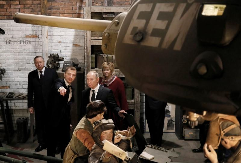 Russian President Vladimir Putin visits an exhibition depicting an armament repair shop at 3D panorama 'Memory speaks. The road through the war' in St.Petersburg