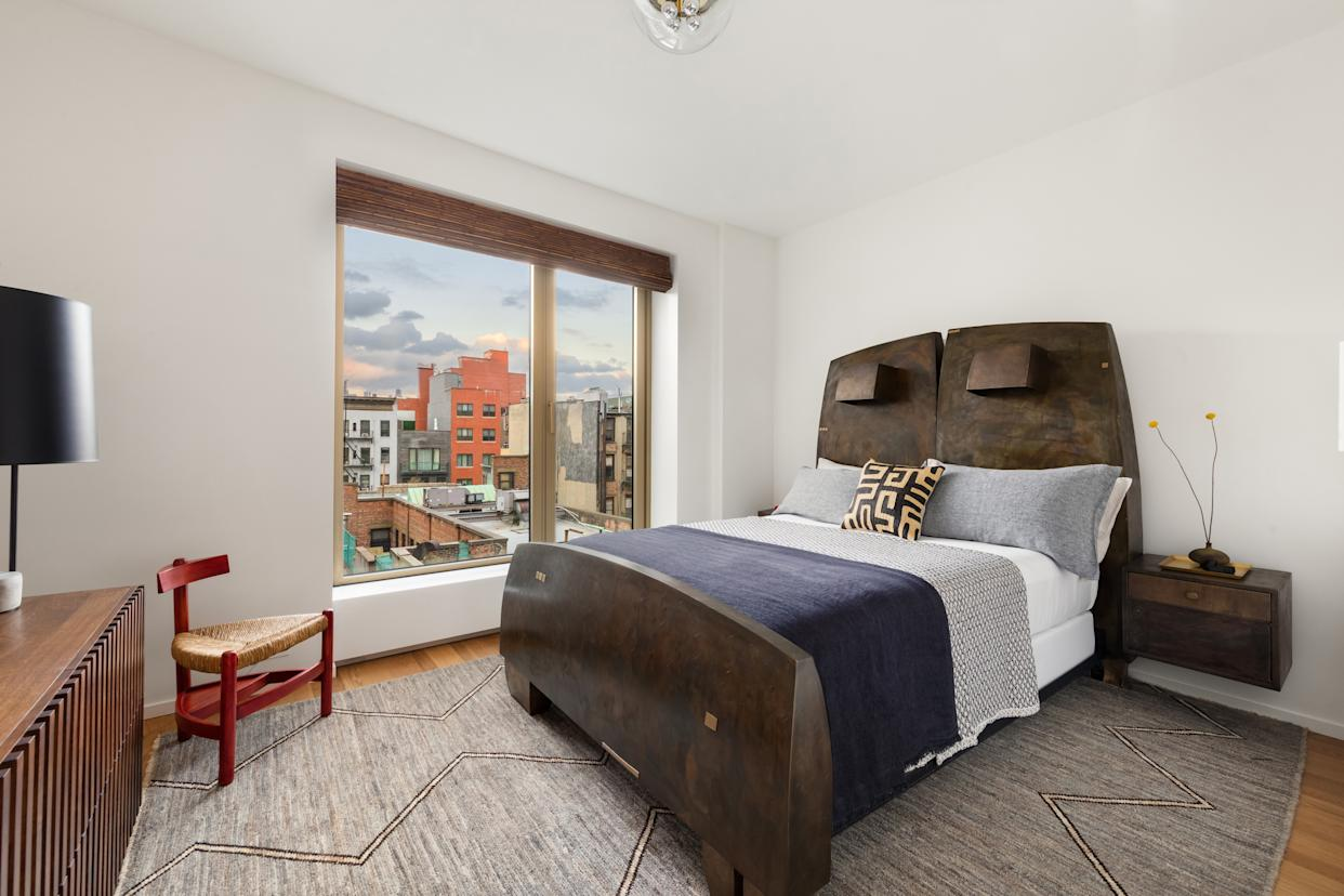 """<div class=""""caption""""> In the guest bedroom, metal artist Gary Magakis designed a sculptural bed. Side chair by Wim Den Boon; rug from Mansour Modern. </div>"""