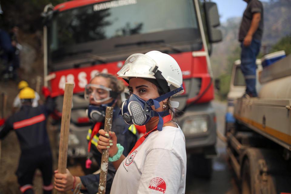 Turkish volunteers stand as they fight wildfires in Turgut village, near tourist resort of Marmaris, Mugla, Turkey, Wednesday, Aug. 4, 2021. As Turkish fire crews pressed ahead Tuesday with their weeklong battle against blazes tearing through forests and villages on the country's southern coast, President Recep Tayyip Erdogan's government faced increased criticism over its apparent poor response and inadequate preparedness for large-scale wildfires.(AP Photo/Emre Tazegul)