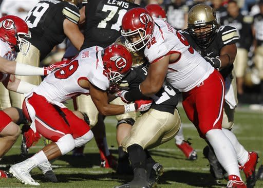 Colorado tailback Tony Jones, center, is stopped at the line of scrimmage by Utah defensive back Reggie Topps, left, and defensive tackle Star Lotulelei during the second quarter of an NCAA college football game on Friday, Nov. 23, 2012, in Boulder, Colo. (AP Photo/David Zalubowski)