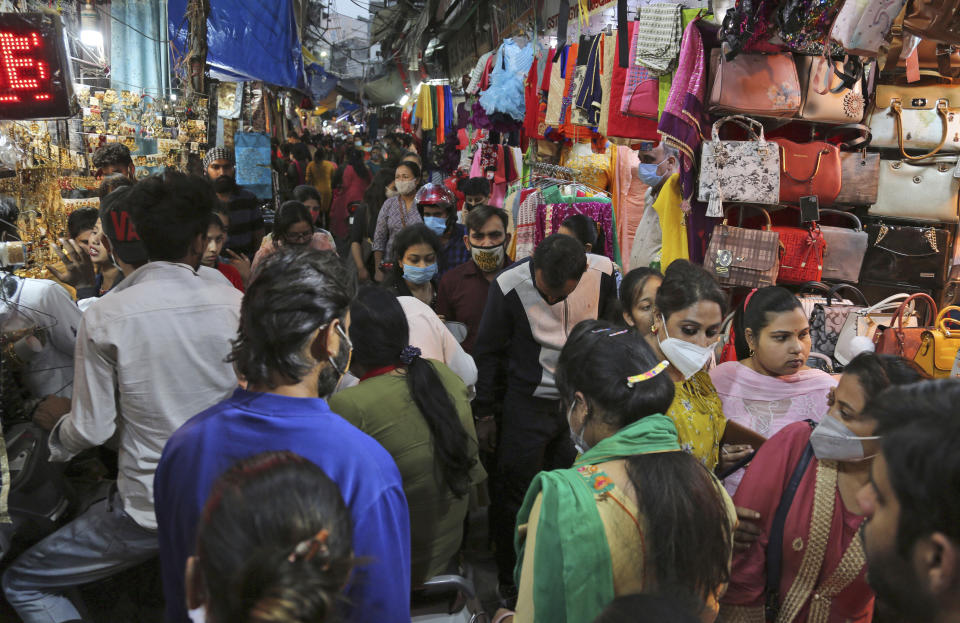 People wearing masks as a precaution against the coronavirus shop at a market on the eve of Karwa Chauth Hindu festival in Jammu, India, Tuesday, Nov. 3, 2020. Married Hindu women observe a day long fast for the health and long life of their husbands on this day. Karwa Chauth will be celebrated on Nov. 4. (AP Photo/Channi Anand)