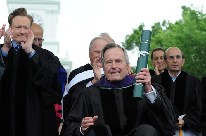 <p>Former President George H.W. Bush holds an honorary doctor of laws degree from Dartmouth College, presented to him during commencement exercises at the college in Hanover, N.H., June 12, 2011. Talk show host Conan O'Brien looks on at left. (Photo: Jason R. Henske/AP) </p>