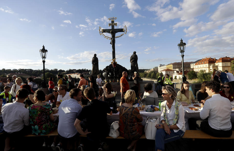 FILE - In this Tuesday, June 30, 2020 file photo, residents sit to dine on a 500 meter long table set on the medieval Charles Bridge, after restrictions were eased following the coronavirus pandemic in Prague, Czech Republic. (AP Photo/Petr David Josek, File)