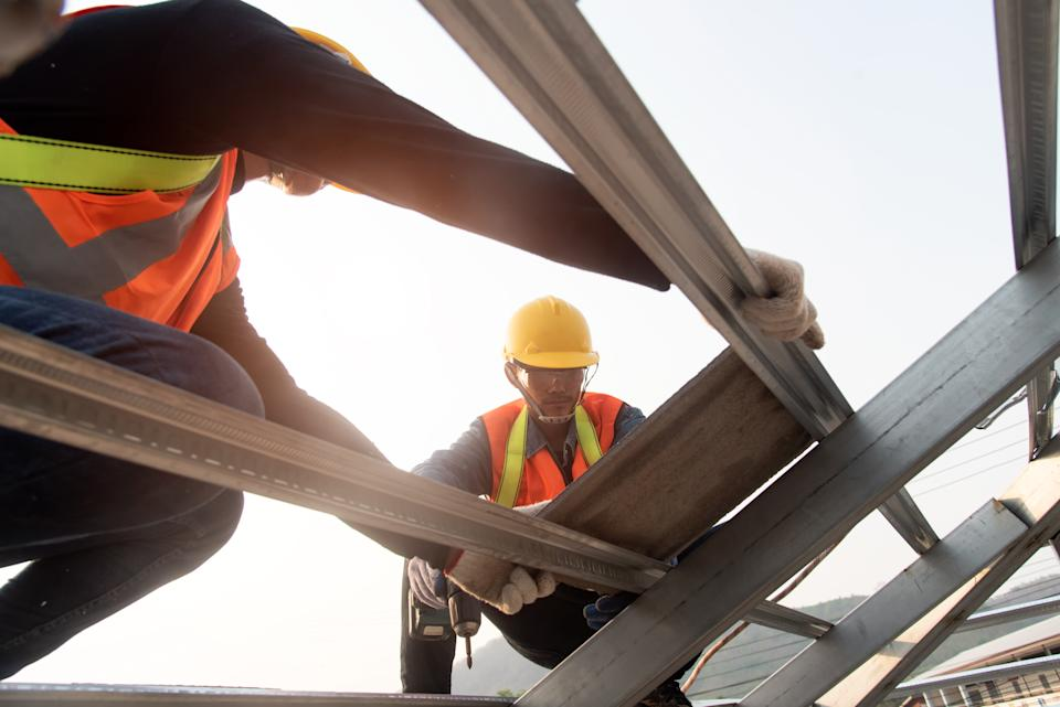 Construction Industry. Roofer with Ceramic Tiles in Hands. Roof Worker Closeup. House Rooftop Covering  Roof construction.