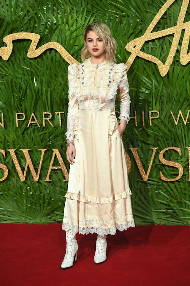 <p>Selena Gomez made her ruffle dress seem a little less sweet with edgy white boots and a dark lip. (Photo: Getty Images) </p>